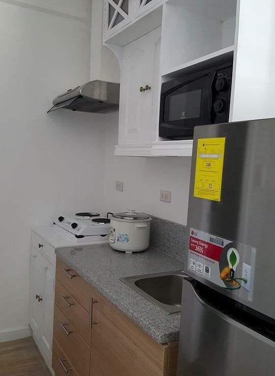 a06-kitchen-with-built-in-french-cabinets-ref-cooking-range-and-microwave-with-kitchen-utensils